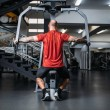 Muscular athlete on exercise machine in gym, back ...