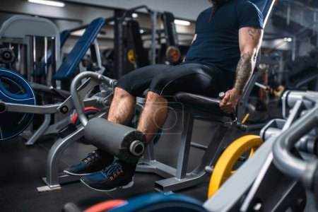Photo for Muscular male person trains legs on exercise machine, training in gym. Bearded man on workout in sport club, healthy lifestyle - Royalty Free Image