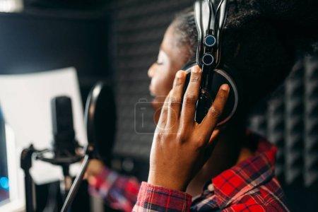 Photo pour Chanteuse dans les chansons de casque d'écoute en studio d'enregistrement audio. Musicien écoute composition, musique professionnelle - image libre de droit