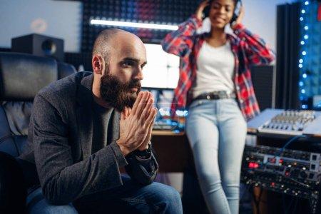 Photo pour Son producteur et chanteuse dans casque écoute composition en studio d'enregistrement. Audio professionnel et la musique, mélange de technologie - image libre de droit