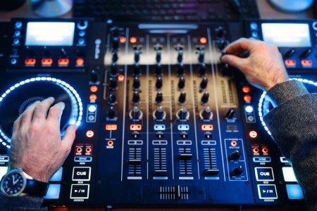 Photo pour Son opérateur remet le panneau de contrôle à distance dans le studio d'enregistrement. Musicien à la table de mixage, traitement audio professionnel - image libre de droit