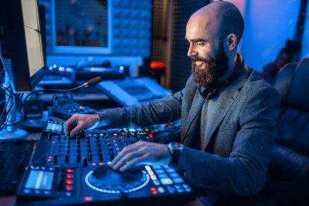 Photo pour Son opérateur vers la télécommande dans le studio d'enregistrement. Musicien à la table de mixage, mixage audio professionnel - image libre de droit