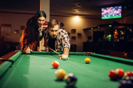 Family couple plays in billiard room. Man and woman leisures, american pool game in sport bar, male player aiming to shot