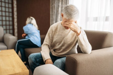 Photo for Adult couple at home, family quarrel or conflict. Mature husband and wife sitting on couch with their backs to each other, problems in relationship - Royalty Free Image