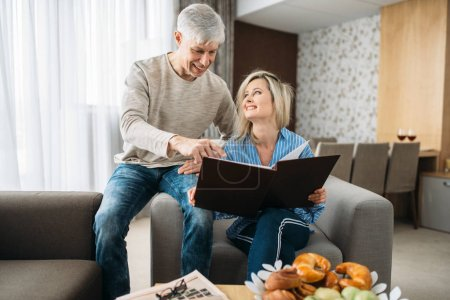 Photo for Mature couple sitting on couch and looking at old photo album, happy family. Adult husband and wife resting at home - Royalty Free Image