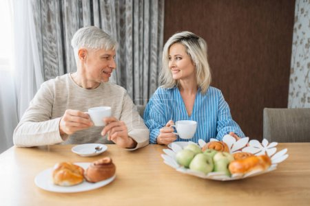 Photo for Breakfast of adult love couple at home. Mature husband and wife sitting in the kitchen, happy family, man and woman drinks coffee at the table with fruits - Royalty Free Image