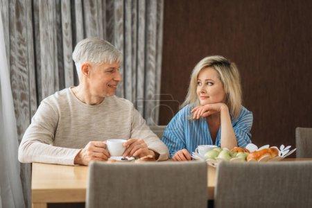 Photo pour Petit déjeuner adulte amour couple à la maison. Mature mari et femme assise dans la cuisine, la mature héhé, le café de boissons homme et femme à la table avec fruits - image libre de droit