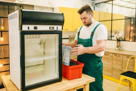 Photo pour Travailleur avec réfrigérateur de réparation boîte à outils à la maison. Réparation de l'occupation du réfrigérateur, un service technique professionnel - image libre de droit