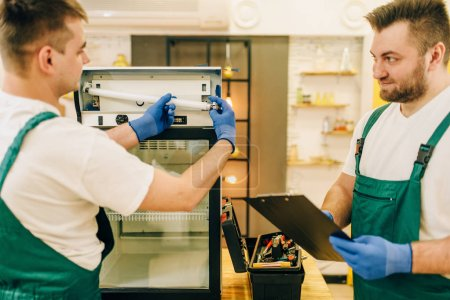 Photo for Two technicians in uniform repair refrigerator at home. Repairing of fridge occupation, professional service - Royalty Free Image