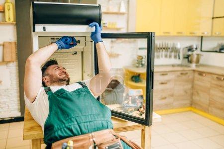 Photo pour Travailleur dans les gants et uniforme réparation réfrigérateur à la maison. Réparation de l'occupation de frigo, service professionnel - image libre de droit