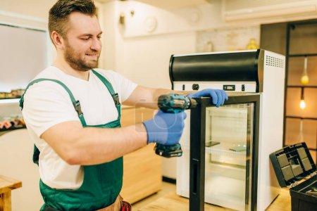 Photo pour Travailleur avec tournevis réparer la porte du réfrigérateur à la maison. Réparation de l'occupation du réfrigérateur, service professionnel - image libre de droit