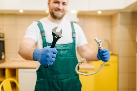 Photo for Plumber in uniform holds wrench, handyman. Professional worker makes repairs around the house, home repairing service - Royalty Free Image