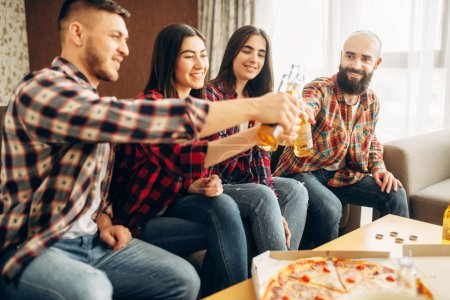 Photo for Smiling friends clink bottles with beer at the home party. Good friendship, group of people leisures together. Cheerful company having fun - Royalty Free Image