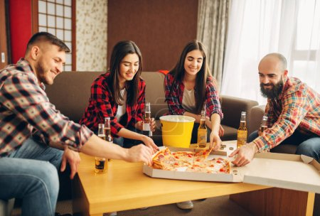 Photo for Smiling friends drinks beer with pizza at the house party. Good friendship, group of people leisures together. Cheerful company having fun - Royalty Free Image