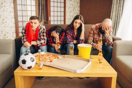 Foto de Los fanáticos del fútbol lamentablemente wathing Teledifusoras en casa. Grupo de personas por perder a su equipo favorito - Imagen libre de derechos