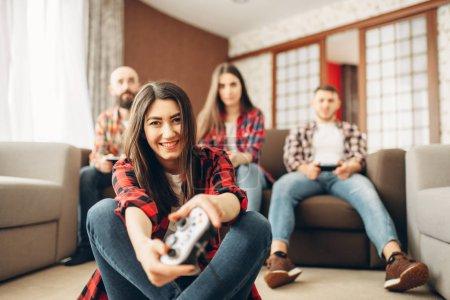 Photo pour Des amis heureux avec joysticks joue console de vidéo à la maison. Groupe de joueurs jouant le jeu, les joueurs ont un concours - image libre de droit