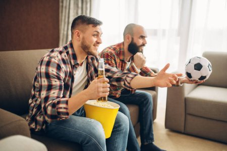 Photo pour Deux mâles football fans visualisées émission de tv à la maison. Amis avec la bière et du pop-corn encourager leur équipe favorite, le match décisif - image libre de droit