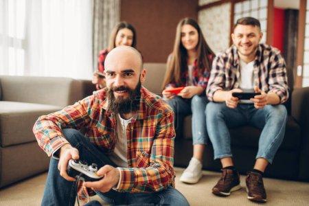 Photo pour Sourire d'amitié avec manettes de jeu joue console tv à la maison. Groupe de joueurs avec joypads jouant des joueurs de jeux vidéo, mâle et femelle avec manettes - image libre de droit