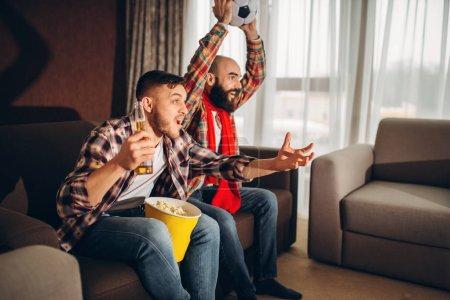 Photo pour Deux mâles football fans visualisées émission de tv à la maison. Amis avec la bière et du pop-corn encourager leur équipe favorite - image libre de droit