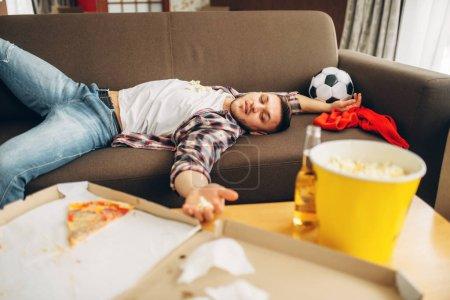 Photo pour Fan de football masculin dormir sur le canapé à la maison. Homme ivre après la célébration de la victoire de l'équipe favorite, parti avec la bière, pizza et popcorn - image libre de droit