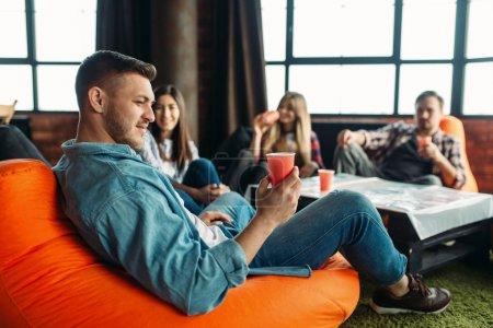 Photo pour Groupe d'étudiants universitaires célèbrent la fin de l'année scolaire. Jeunes avec des boissons à la table dans l'appartement, fête à la maison - image libre de droit
