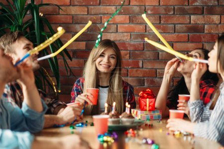 Photo for Group of highschool students celebrating the delivery of the session. Youth in clown caps at the table in the flat, party - Royalty Free Image