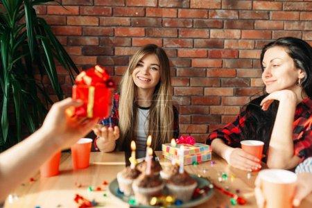 Photo pour Groupe d'élèves du secondaire se donnent mutuellement des cadeaux. Jeunes à la table dans l'appartement, fête à la maison, célébration d'anniversaire - image libre de droit