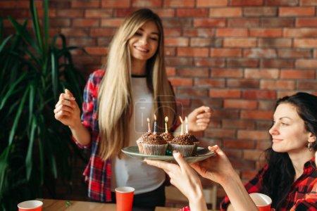 Photo pour Étudiante universitaire reçoit un doux cadeau de ses amis. Jeunes à la table dans l'appartement, fête à la maison, célébration d'anniversaire - image libre de droit