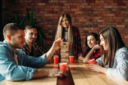 Photo for Smiling friends plays table game at home, selective focus on tower. Board game with wooden blocks requiring high concentration, entertainment for funny company - Royalty Free Image