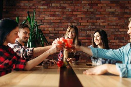 Photo pour Un groupe d'étudiants célèbre l'événement. Jeunes avec des boissons à la table dans le café d'université, partie d'université - image libre de droit