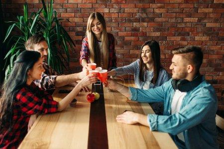 Photo pour Groupe d'étudiants célébrer l'événement. Les jeunes avec des boissons à la table dans le café du collège, fête universitaire - image libre de droit