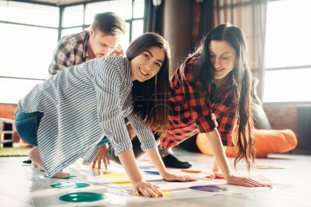 Photo for Group of students playing twister game. Youth in funny poses on the floor, entertainment for active company, friends having fun - Royalty Free Image