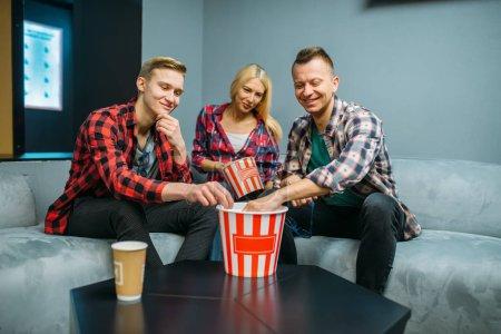 Photo pour Amis mangeant du pop-corn dans la salle de cinéma avant la projection. Jeunes mâles et féminins s'asseyant sur le sofa dans le cinéma - image libre de droit