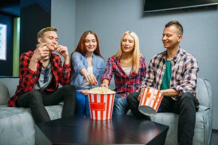 Photo pour Amis mangeant du pop-corn et s'amusant dans la salle de cinéma avant la projection. Jeunes mâles et féminins s'asseyant sur le sofa dans le cinéma - image libre de droit