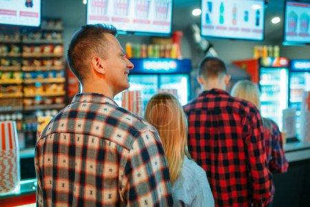 Photo pour Public choisissant la nourriture dans le bar de cinéma avant l'heure de spectacle, vue arrière. Jeunes mâles et femelles dans le théâtre de cinéma - image libre de droit
