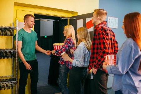 Photo pour L'huissier donne des lunettes devant la salle de cinéma. Jeunes mâles et femelles dans le théâtre de cinéma - image libre de droit