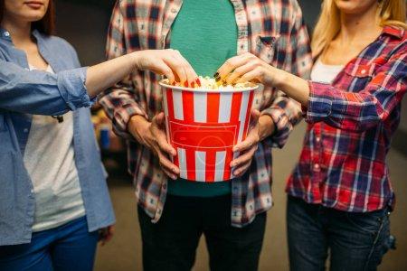 Photo pour Le groupe d'amis pose avec le maïs éclaté dans la salle de cinéma avant l'heure du spectacle. Jeunes mâles et femelles attendant dans le théâtre de cinéma, mode de vie de divertissement - image libre de droit