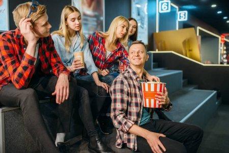 Photo pour Groupe d'amis s'amusant dans la salle de cinéma avant l'heure du spectacle. Jeunes mâles et femelles attendant dans le cinéma - image libre de droit