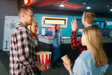 Photo pour Groupe d'amis achetant des billets dans la billetterie de cinéma. Jeunes mâles et femelles attendant dans le théâtre de cinéma, mode de vie de divertissement - image libre de droit