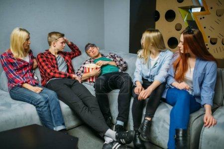 Foto de Grupo de adolescentes comiendo palomitas de maíz y esperando la hora del espectáculo en la sala de cine. Jóvenes masculinos y femeninos sentados en el sofá en el cine - Imagen libre de derechos