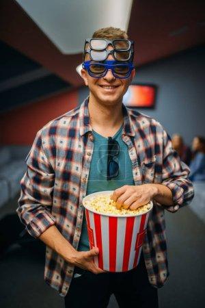 Photo pour Le spectateur masculin dans les lunettes 3D tient le maïs éclaté dans la salle de cinéma avant l'heure du spectacle. Homme dans le théâtre de cinéma, mode de vie de divertissement - image libre de droit