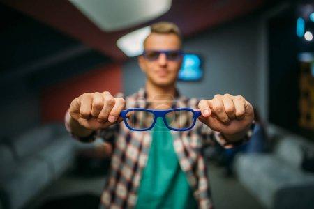 Photo pour Le spectateur masculin montre des lunettes 3D dans la salle de cinéma avant l'heure du spectacle. Homme dans le théâtre de cinéma, mode de vie de divertissement - image libre de droit