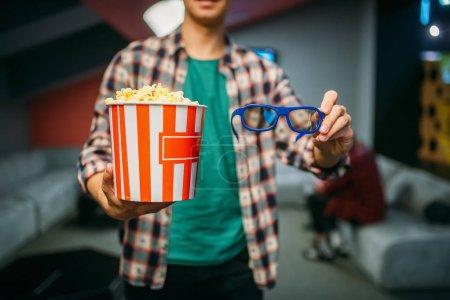 Foto de Espectador masculino con vasos 3D y palomitas de maíz en la sala de cine antes de la hora del espectáculo. Hombre en el cine, estilo de vida de entretenimiento - Imagen libre de derechos