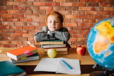 Photo pour Écolière sérieuse avec des manuels pose à la table. Étudiante lisant un livre au bureau, jeune fille faisant ses devoirs - image libre de droit