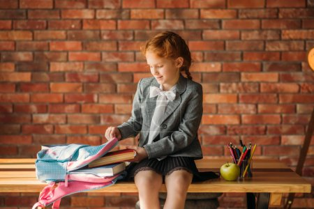 Photo for Cute schoolgirl puts textbook into the schoolbag, side view. Female pupil with backpack, desk with textbooks, apple and globe on backgrpund, young girl in the school - Royalty Free Image