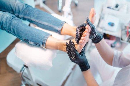 Photo pour Salon d'esthéticienne, massage des pieds. Soin des ongles pour cliente en institut de beauté, médecin en gants travaille avec les jambes du client - image libre de droit