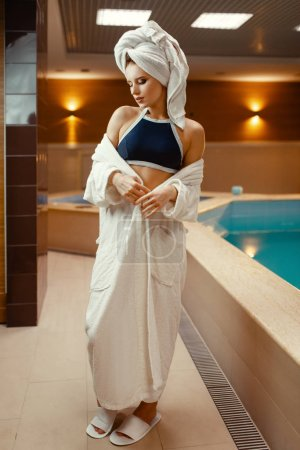 Photo for Sexy lady in towel on the head and body at the pool side indoors. Swimming and relaxation, healthy lifestyle, attractive woman in spa salon - Royalty Free Image