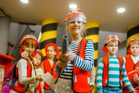 Photo for Child in helmet and uniform with hose in hands playing fireman, playroom indoor. Kids lerning firefighter profession. Children lifeguards, little heroes in equipment on playground - Royalty Free Image