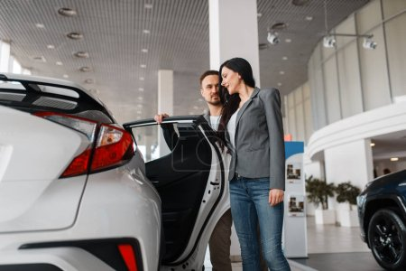 Photo for Couple choosing new car in showroom. Male and female customers looks vehicle in dealership, automobile sale, auto purchase - Royalty Free Image