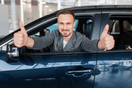 Photo pour Homme assis dans une nouvelle voiture et montre pouces levés, showroom. Client choisissant le véhicule chez le concessionnaire, vente d'automobiles, achat d'automobiles - image libre de droit